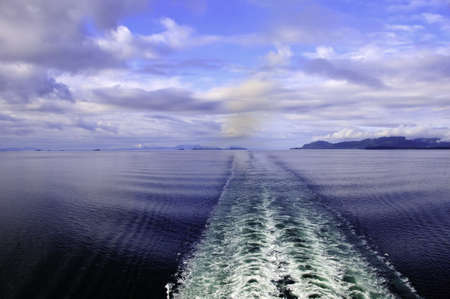 The wake behind a cruise ship with mountains in the background