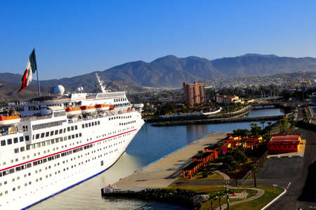A cruise ship docking at Ensendad Mexico with the Mexican Flag flying in the background Stock Photo - 13182365