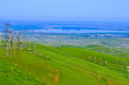 Powerlines, windturbines and rolling green hills photo