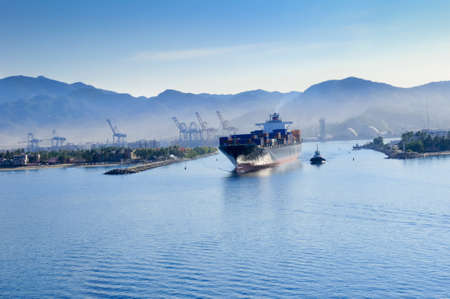 A container ship leaving the harbor at manzanillo, Mexico, with a tug boat