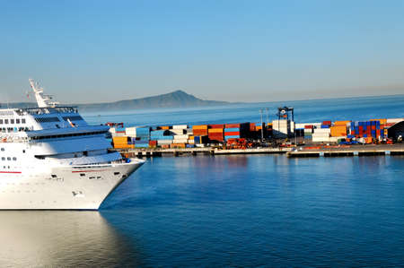 A cruise ship coming into port at ensenada, Mexico with shipping containers in the background