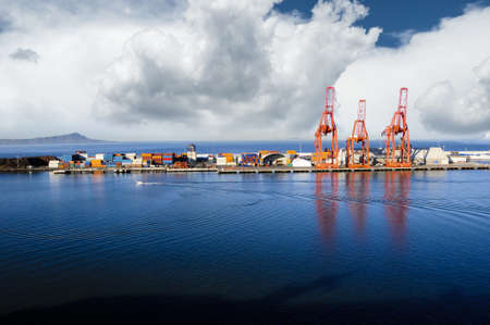 Bright red shipping cranes in Ensenada, Mexico with shipping containers