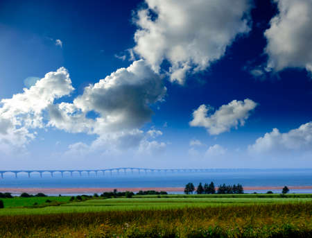 confederation: Confederation bridge at Prince Edward Island, Canada with a hay field in foreground