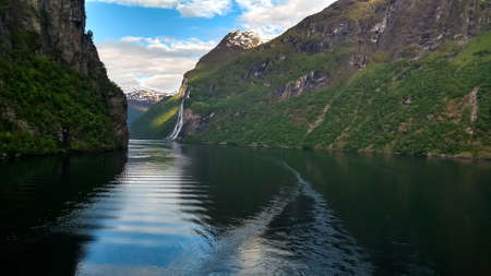 Cruising through the Fjords of Norway to Geiranger, past waterfalls.