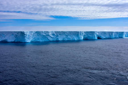 Blue iceberg with caves floating in Admiralty bay, Antarctica.