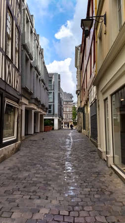 A cobblestone street with store fronts on each side in Rouen France.