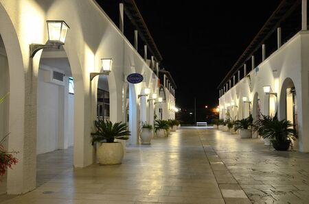 Illuminated night street with the arches and walls, lit brightly, and a marble pavement. Old-fashioned night street with low-rise buildings