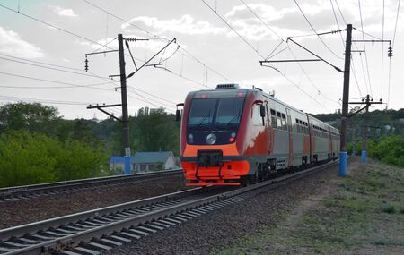 New Russian commuter, colored in red and grey, goes by rail. A diesel-electric train destination to Voronezh rides by suburb at dusk