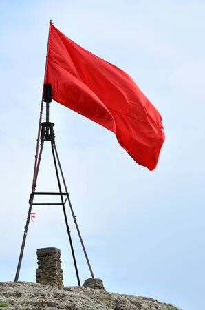 Red flag at the top of high mountain on overcast day. A scarlet banner waving in the wind. The vivid red-colored flag on the foreground of cloudy sky