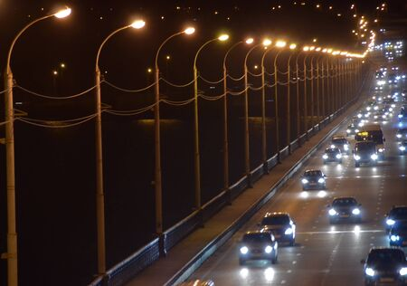 Night city: cars with the headlights on the road. City traffic and street lanterns on the broad bridge Stock Photo