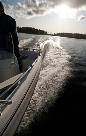 Motorboat leaving a wash after it on Baltic sea  gulf of Bothnia  waves motor cruising sun clouds breeze wind autumn Stock Photo