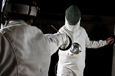 fencers: swordsmen fencing.