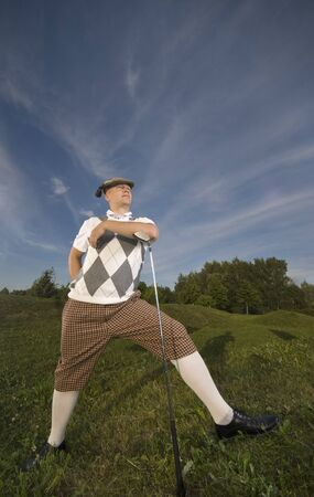 Funny golfer leaning on golf club enjoying the sun. Stock Photo