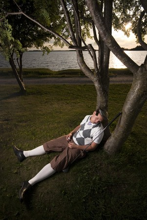 Funny picture of a golf player sleeping under trees. Holding a golf ball in his hand.