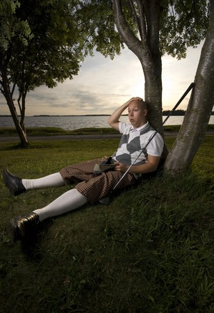 Exhausted golfer taking a break.  Resting under tree.