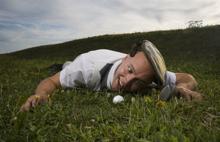 Crazy golfer gazing at golf ball in the rough.