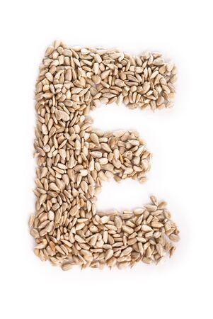 Alphabet E made of sunflower seeds. Stock Photo