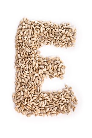 Alphabet E made of sunflower seeds. Stock Photo