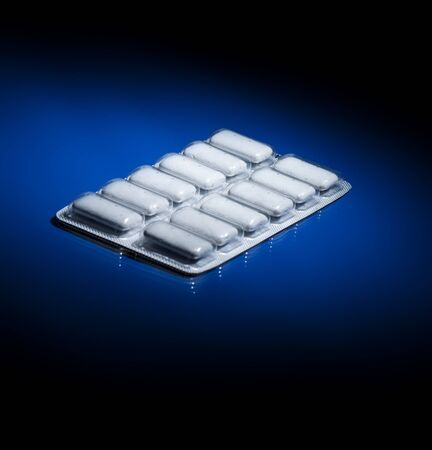 nicotine: A package of nicotine gum on dark blue background fading to black.