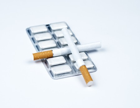 Nicotine gum and crossed tobacco. Stock Photo