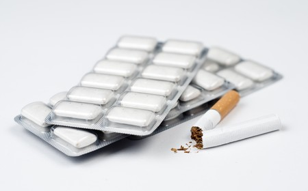 goma de mascar: Fotograf�a conceptual para dejar de fumar. Cigarrillos roto en frente de los discos de goma de mascar de nicotina.