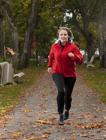 beatuful: Beautiful female athlete running in park on a beatuful autumn day.