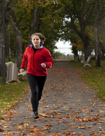 Beautiful female athlete running in park on a beatuful autumn day.