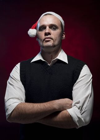 an evil christmas elf portrait with makeup and blood splash on his face stock photo - Christmas Elf Makeup