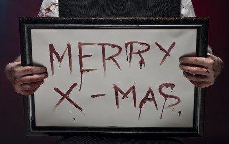 Bloody fingers hold a Merry christmas sign, written with blood. Stock Photo