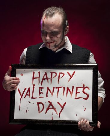 A blood stained man holding a happy valentines sign written with blood.