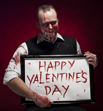 A blood stained man holding a happy valentine's sign written with blood. Stock Photo - 8703289