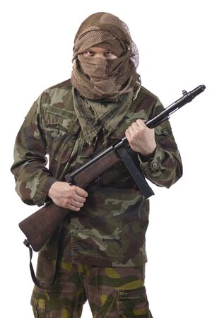 Camouflaged guerrilla soldier with hidden face and a machine gun