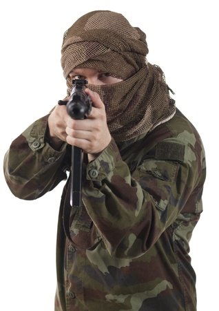 armed: Camouflaged guerrilla soldier with hidden face and a machine gun aiming at camera. Isolated on white background.