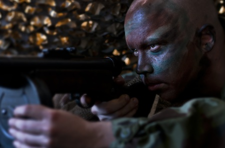 guerrilla warfare: Camouflaged soldier aiming from ambush.