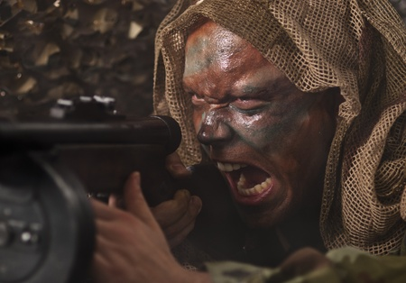 A camouflaged guerrilla soldier screaming while shooting from ambush.