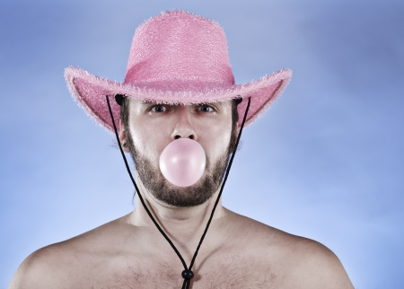 Funny cowboy in pink cowboy hat blowing ping ball of chewing gum