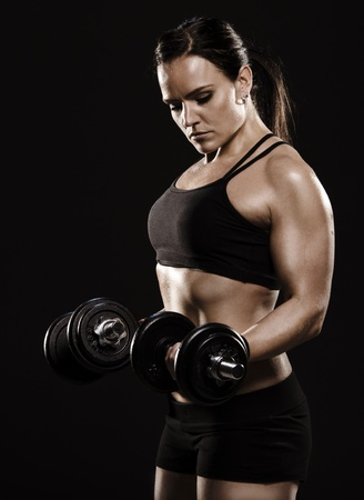 A studio shot of a beautiful fitness woman working out with dumbbells