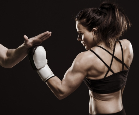 woman boxing gloves: A studio shot of beautiful fitness woman training boxing