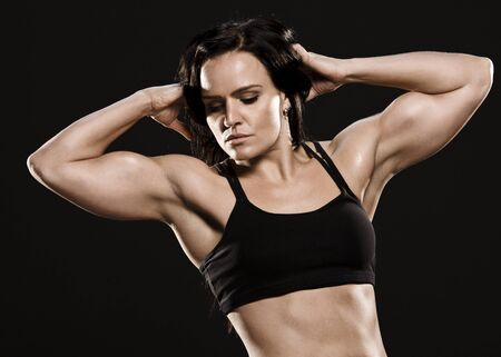 Beautiful well trained fitness brunette posing and showing biceps  photo