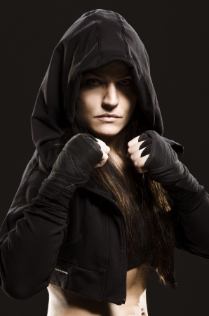 Studio shot of a beautiful serious woman getting ready to fight