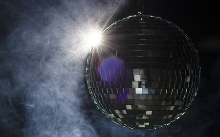 A disco ball with light flare and smoke  A nightlife image to be used as example on party fliers  Stock Photo