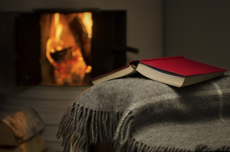 downshift: Peaceful and warm image of open book resting on a arm rest of a couch  Warm fireplace on background