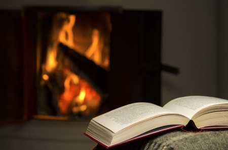 Peaceful and warm image of open book resting on a arm rest of a couch  Warm fireplace on background Stock Photo - 17432089