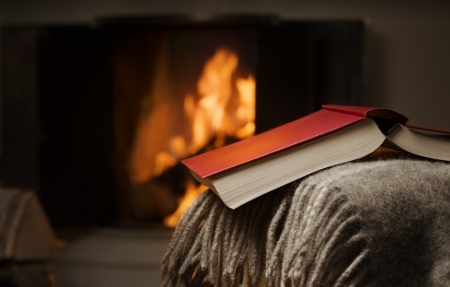 Peaceful and warm image of open book resting on a arm rest of a couch  Warm fireplace on background  Stock Photo - 17427448