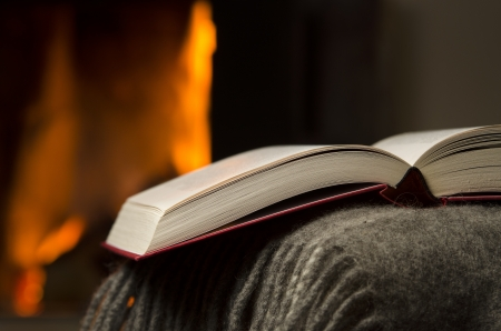 downshift: Peaceful and warm closeup of open book resting on a arm rest of a couch  Warm fireplace on background