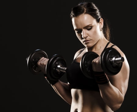 Beautiful muscular woman doing a biceps workout with dumbbells