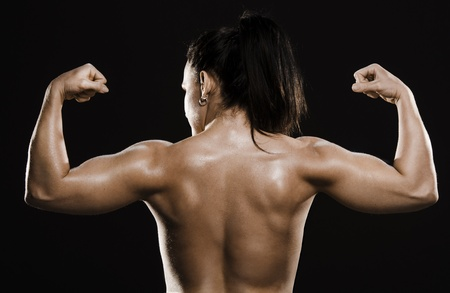 Fit topless woman showing back muscles  Shot from behind