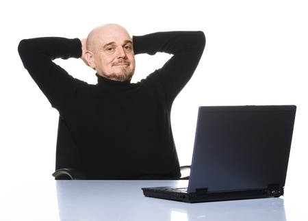 Casual older man smiling with hands behind his head and  laptop computer in front of him on a table