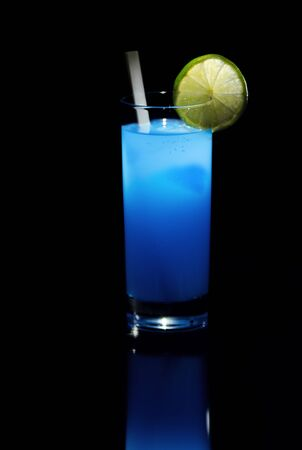 Blue cold and refreshing drink with a white stick and lime  Visible reflection