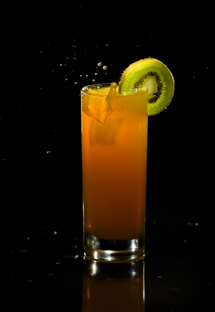 Refreshing orange drink on a reflective surface  Kiwi fruit on rim  Splashes of liquid when a ice cube is dropped in to the drink